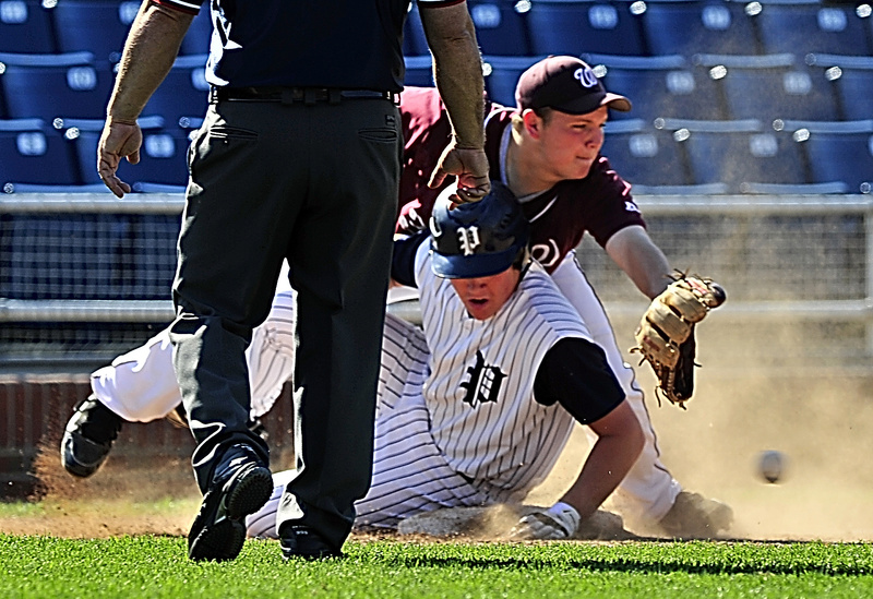 Scott Briggs of Portland slides safely into third base Tuesday as Robert Hamilton of Windham attempts to control a throw from the outfield during their Telegram League game at Hadlock Field. Windham scored four runs in the fifth inning for a 6-3 victory.