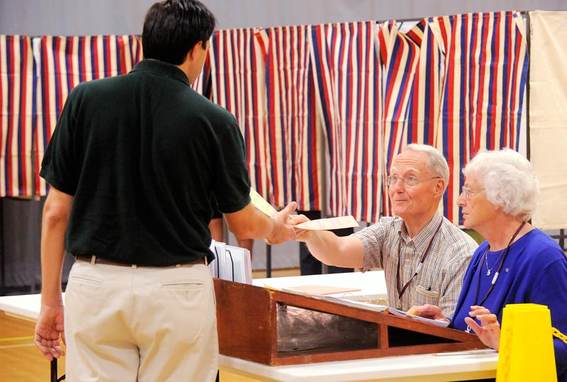 Cape Elizabeth voters cast their ballets at Cape Elizabeth High School on Tuesday morning. Assistant town clerks Scott Berry and Margaret Davenport hand a ballot to a Cape voter. (Photo by JohnEwing/ Staff photographer)