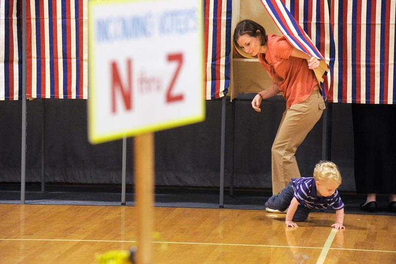 Cape Elizabeth voters cast their ballets at Cape Elizabeth High School on Tuesday morning. Two year old Toby Noonan makes his break from a voting booth his mom, Gretchen Noonan, was voting at. (Photo by JohnEwing/ Staff photographer)