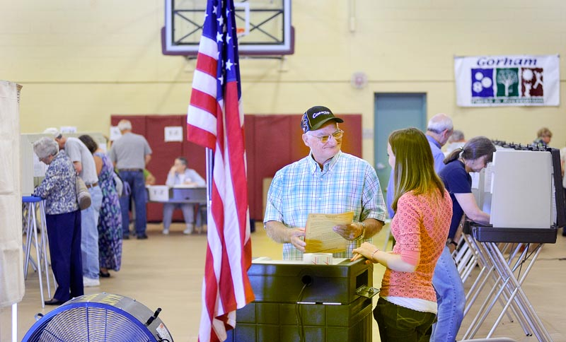 Richard Moody shares a light moment with ballot clerk Melissa Deering as he casts his votes in the Gorham Municipal Center today. (John Patriquin /Staff Photographer)