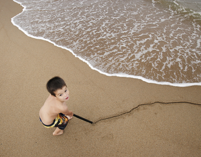 T.J. Ashcraft, 4, a local resident, draws a line in the sand at Ocean Park. The sun is expected to return today with temperatures reaching the mid-70s.