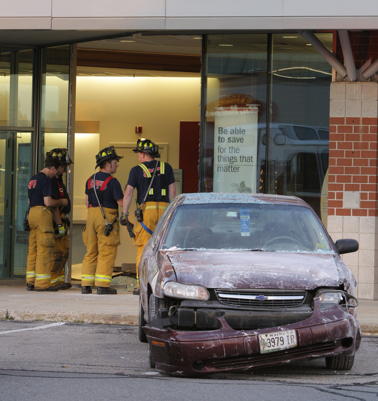 A Chevy Malibu sits near the entrance of the Bank of America at 50 Market St. in South Portland on Monday evening. The car crashed through a window and then partially through an interior wall near the ATM. The driver got his foot stuck on the gas pedal, police said.