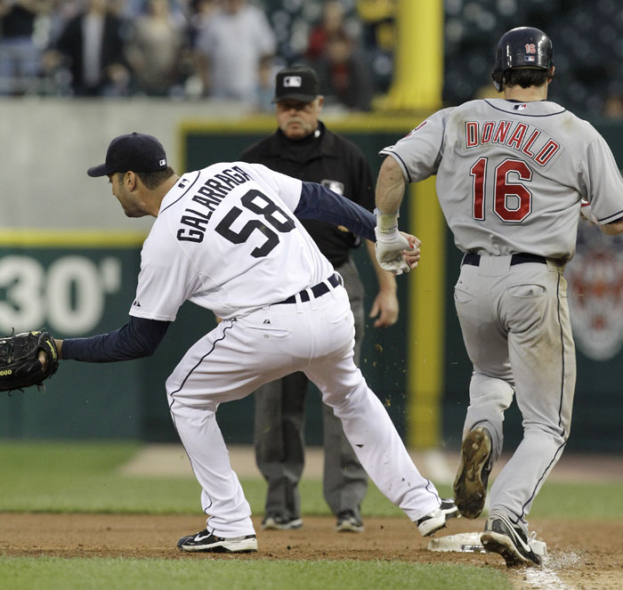 Detroit Tigers pitcher Armando Galarraga (58) covers first base as Cleveland Indians' Jason Donald, right, runs to the base and umpire Jim Joyce looks on in the ninth inning of a baseball game in Detroit Wednesday. Joyce called Donald safe and Galarraga lost his bid for a perfect game with two outs in the ninth inning on the disputed call at first base. Detroit won 3-0.