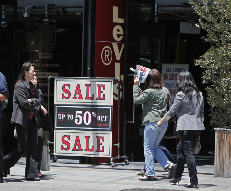 People walk by a sale sign at the entrance of the Levi's store on Union Square in San Francisco. Retail sales plunged in May by the largest amount in eight months as consumers slashed spending on everything from cars to clothing.