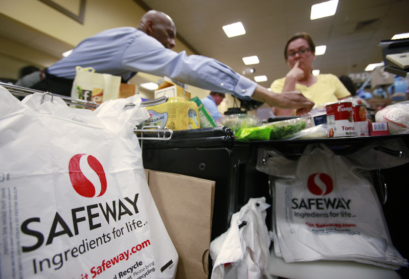 "A Safeway worker, left, bags items for a grocery customer in San Ramon, Calif. The issue of a growing U.S. deficit has made some lawmakers leery of adding more debt in the form of stimulus funding, but ""it is way too early to apply the fiscal brakes,"" counters economist Zach Pandl."