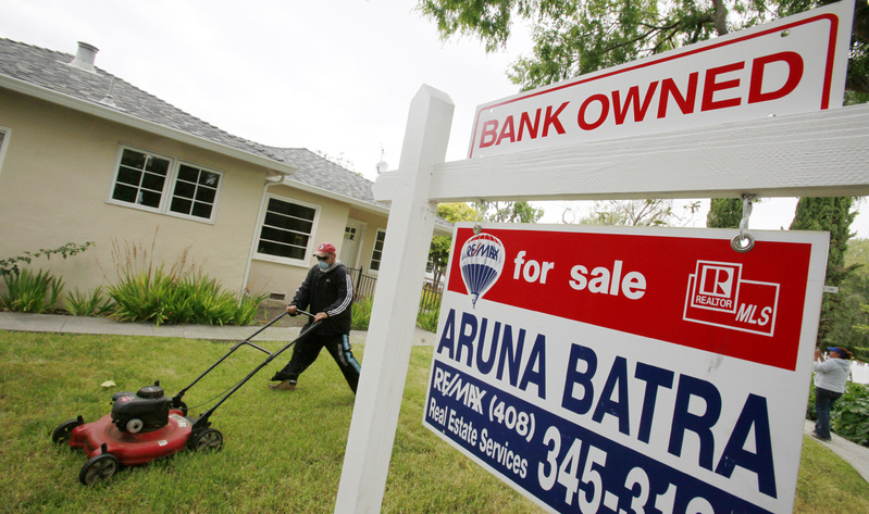 A gardener cuts the lawn at a foreclosed home in Palo Alto, Calif. Tax credits that help boost sales earlier in the year have expired, adding to downward pressure on the market.