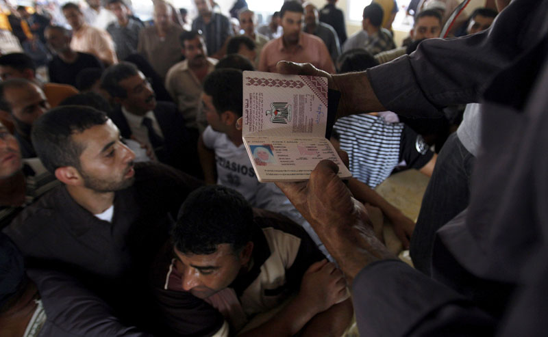 A Hamas border official holds the passport of a Palestinian woman waiting to cross into Egypt through the Rafah border crossing, southern Gaza Strip, today. An Egyptian official says the government is temporarily lifting its blockade of the Gaza Strip to allow aid into the area a day after Israel raided an international flotilla carrying supplies to the Palestinian territory, and killed nine activists.