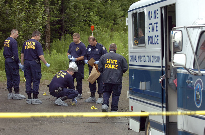 Maine State Police Evidence Response Team members investigate the scene of a triple homicide in Amity.