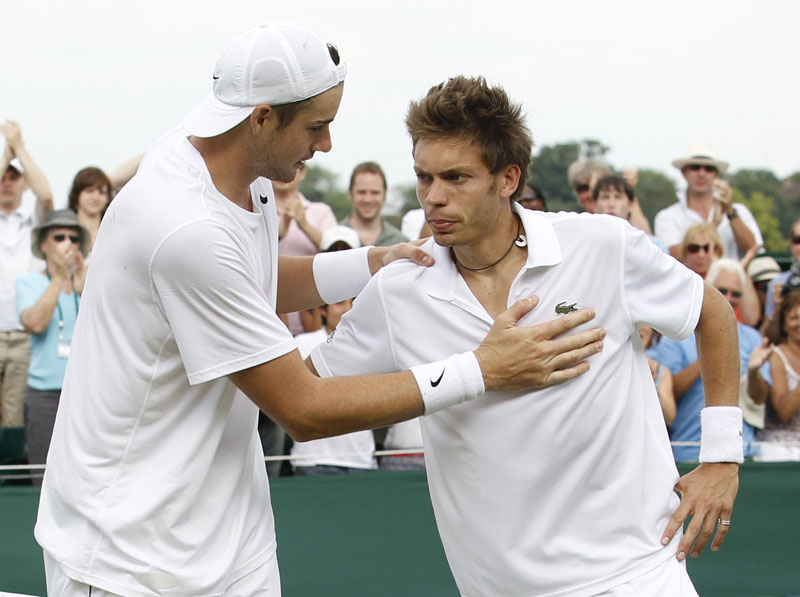 American John Isner, left, consoles France's Nicolas Mahut at the end of their epic men's singles match at the All England Lawn Tennis Championships at Wimbledon today.