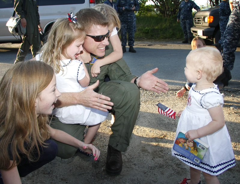 Lt. Cmdr. Greg Smith of Brunswick is welcomed home by his daughters, from left, Madeline, 11, Mary, 3, Riley, 8, and Rhyse, 1, at the Portland International Jetport. Smith is a member of VP-26, a Navy squadron that flew out of Brunswick Naval Air Station on Nov. 28 and returned Monday after a six-month deployment in Europe, Africa and Central America.