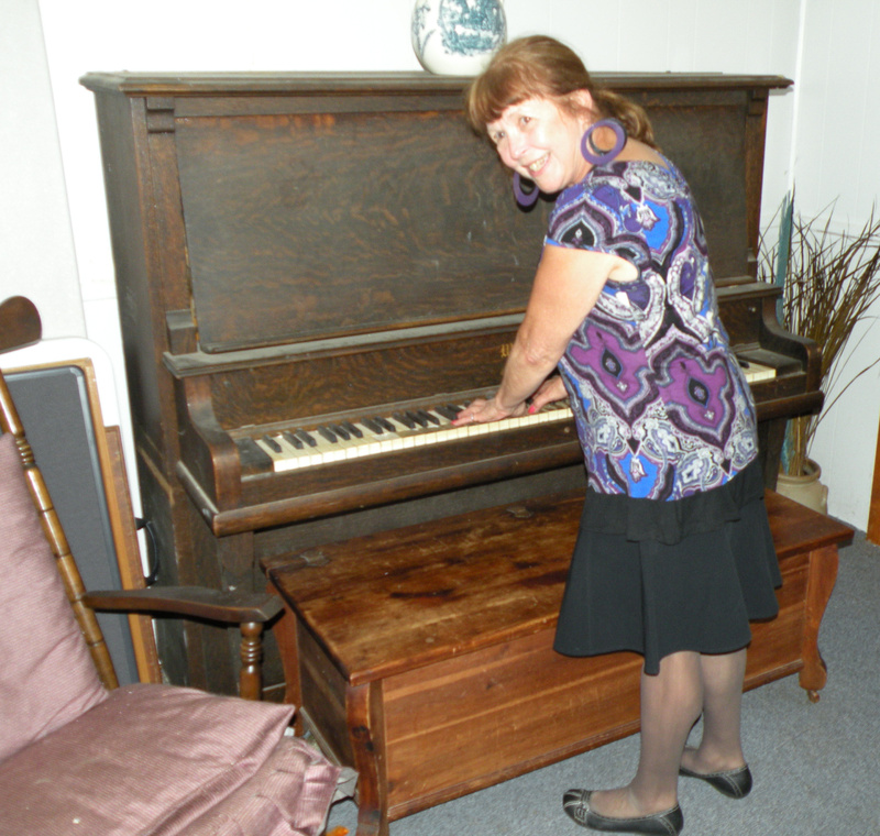 Marilyn Lacombe Snipe poses with an antique piano once played at Waterville's Bijou Theater during silent movies.