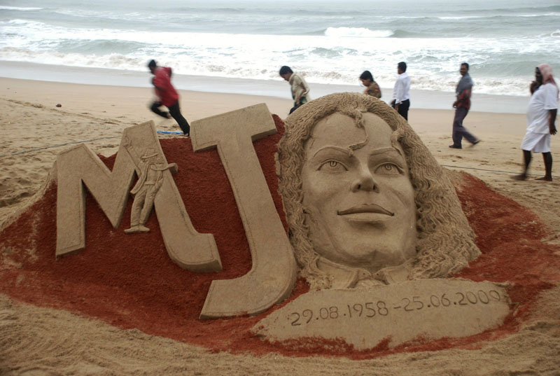 People walk past a sand sculpture of Michael Jackson created to mark the first anniversary of his death, at the Bay of Bengal coast, in Puri, Orissa state, India, Thursday.
