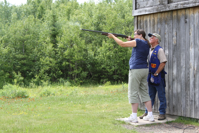 Intructor Brad Varney looks over the shoulder of novice skeet shooter Wendy Almeida as she fires at a clay target at Varney's range in Richmond.