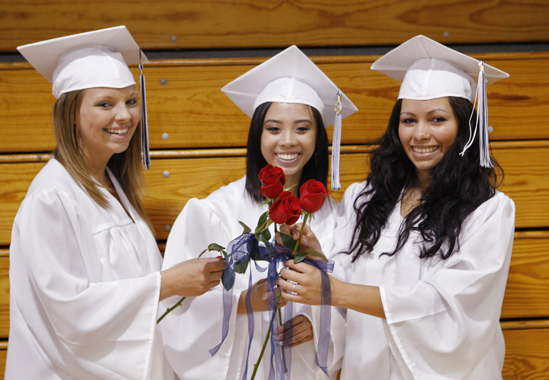Portland High School seniors Natasha LeClair, left, Rose Pham and Yuri Shepard-Kegl hold their roses together before Portland High's graduation ceremony today.