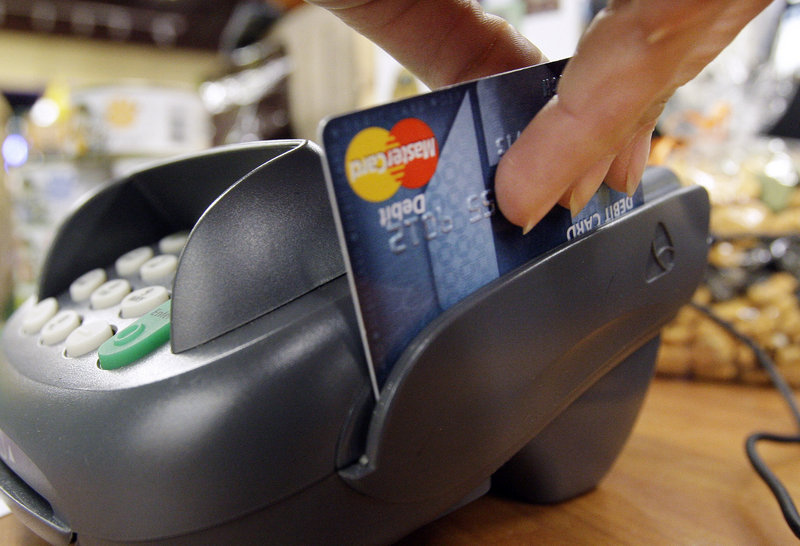 A customer swipes a MasterCard debit card through a machine while checking out at a shop in Seattle. Battle lines are being drawn in Congress over debit card fees.