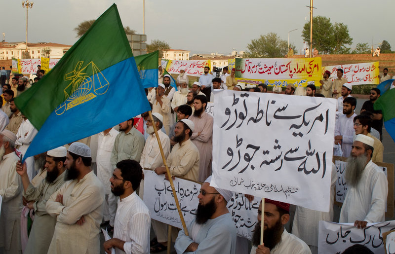 """Supporters of Tanzeem-e-Islami, a Pakistani religious party, listen at a rally against a Facebook page in Islamabad, Pakistan, on Saturday. The placard at front right reads: """"Disconnect relations with America and connect with God."""""""