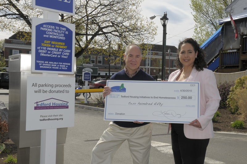 Larissa Darcy, vice president of Savings Bank of Maine, presents Don Kniseley, executive director of Tedford Housing, with a $250 check, the proceeds from the bank's Brunswick parking area.