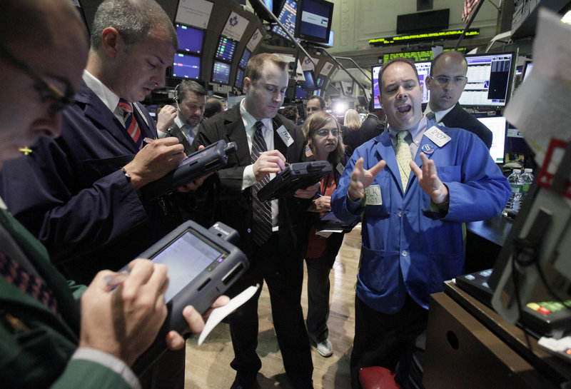 Specialist Thomas Warshaw, foreground right, directs trades in shares of BP on the floor of the New York Stock Exchange. Led by BP's stock plunge, the Dow lost 112 points Tuesday.