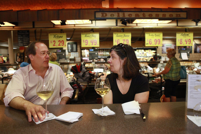 George Hruby, left, and his wife, Alison Hruby, of Fairfax, Va., enjoy a glass of wine at the delicatessen inside the Market Cafe in the Wegmans grocery store in Fairfax, Va. Supermarkets are hoping customers will grocery shop, of course, but also stop more often for a low-cost restaurant-style meal.