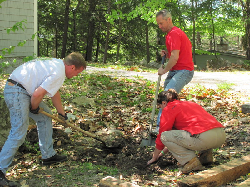 Volunteers do some landscaping work at Camp Sunshine as part of the Harvard Pilgrim Day of Service in May. The team also built a disc golf course for the camp.