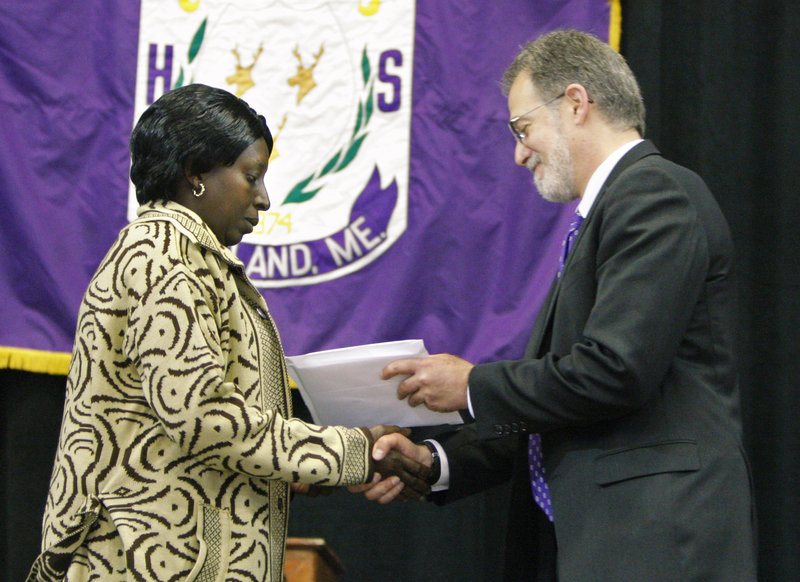 Synforose Rugema receives a diploma on behalf of her son Guy Kitoko, who was killed in a car accident last September.