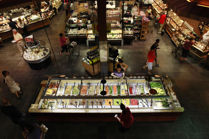 Customers shop at the salad bar for lunch at the Market Cafe in the Wegmans grocery store in Fairfax, Va. The prepared supermarket food available today is a far cry from the modest offerings of fresh coffee, potato salad and rotisserie chickens of years past, as grocery stores try to increase their appeal and customer traffic.