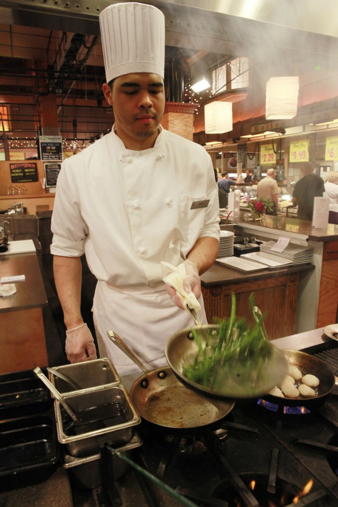 Will Miller prepares Alaskan halibut with pan-seared green beans for customers dining in at the Market Cafe in the Fairfax, Va., Wegmans grocery store.