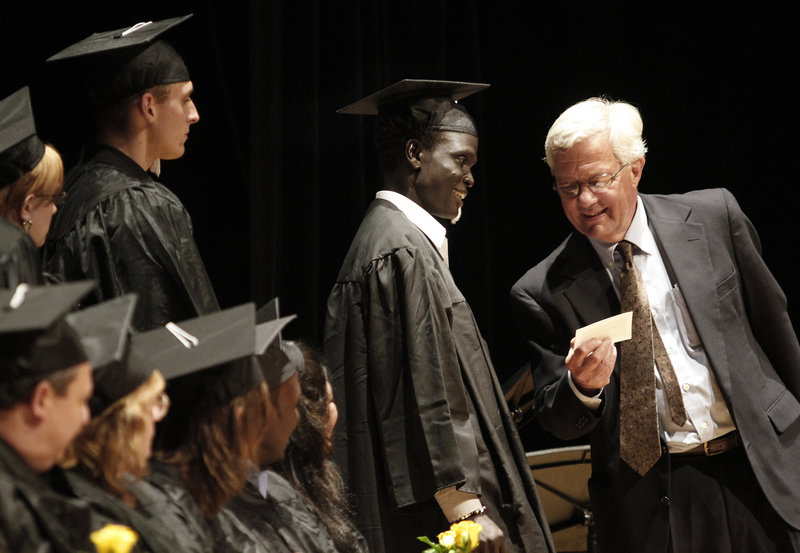 Rob Wood, right, co-director of Portland Adult Education, checks name pronunciation with Tichot Pout Neyail Yei before announcing it during graduation ceremonies.