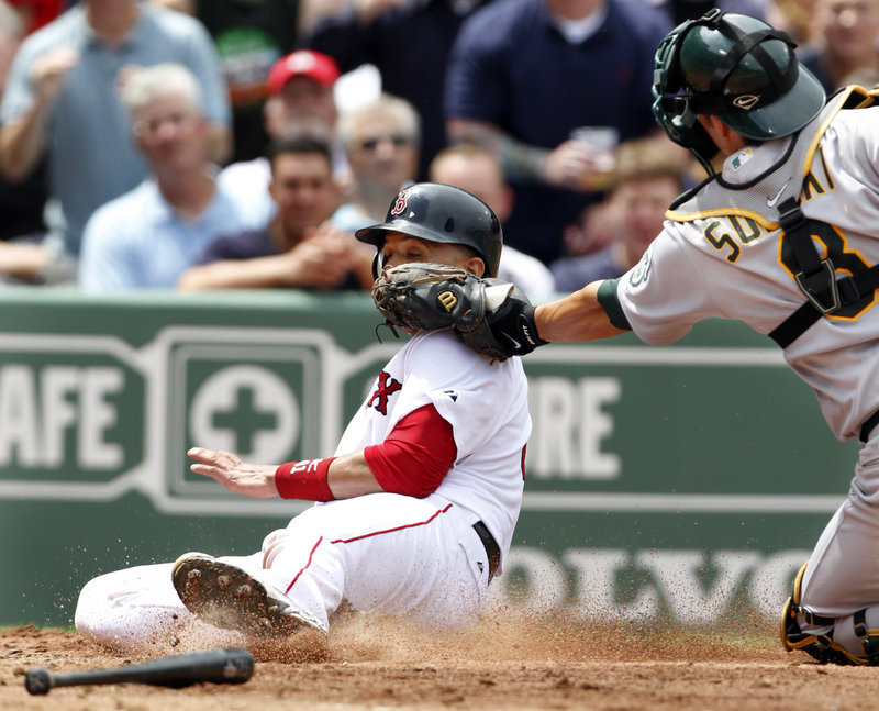 Victor Martinez of the Boston Red Sox is tagged out by Oakland catcher Kurt Suzuki while trying to score on a Kevin Youkilis double in the third inning Thursday. The Red Sox had two runners thrown out at the plate in a 9-8 loss.