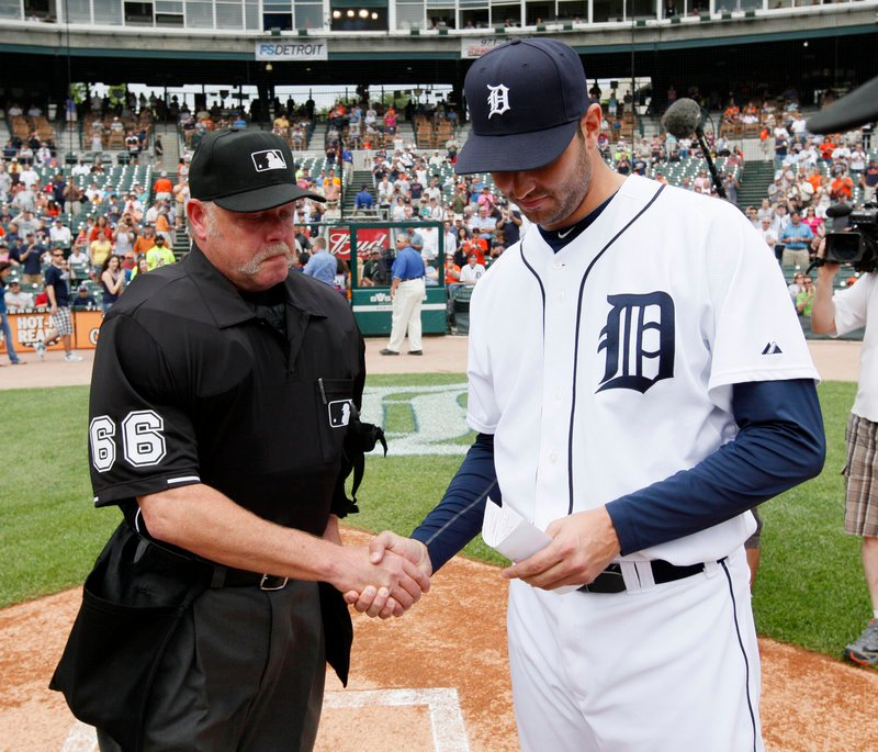 Detroit pitcher Armando Galarraga, who lost his bid for a perfect game on a blown call by umpire Jim Joyce, shakes hands with Joyce while handing over the lineup card Thursday before the Detroit-Cleveland game in Detroit.