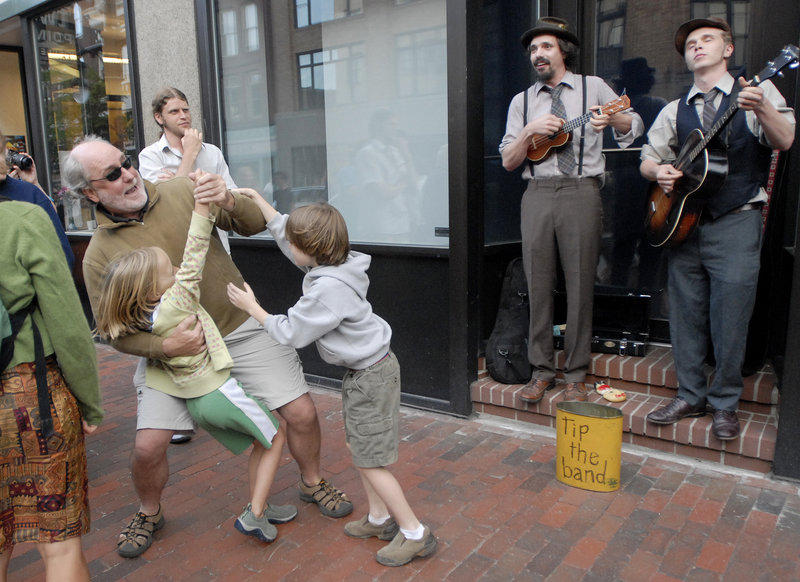 Scott Elliott of Portland dances with Carly Hagelin, 8, of Portland and his son Kieran Elliott, 7, as Tim Findler and Jimmy Dority of Portland perform on Congress Street during the First Friday Art Walk on Friday. Findler is playing a ukulele as Dority plays the tenor guitar.