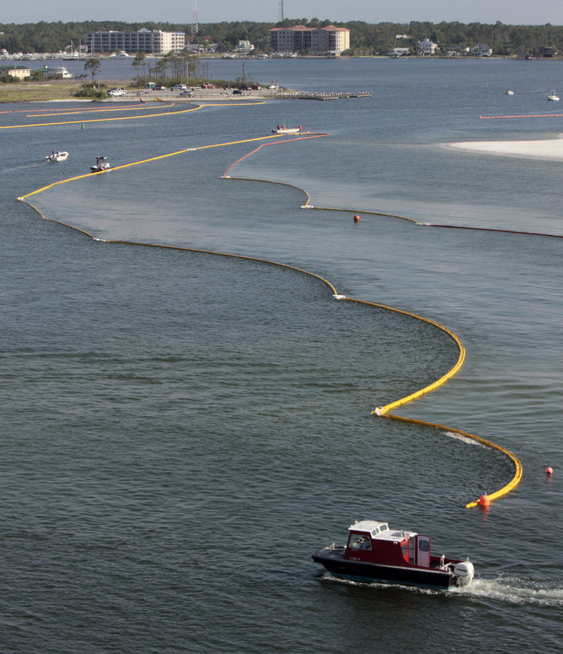 Boats work to secure oil containment booms in the Perdido Pass in Orange Beach, Ala., on Friday. Oil from the Deepwater Horizon oil drilling blowout and explosion that killed 11 workers on April 20 has started washing ashore on Alabama and Florida coast beaches.