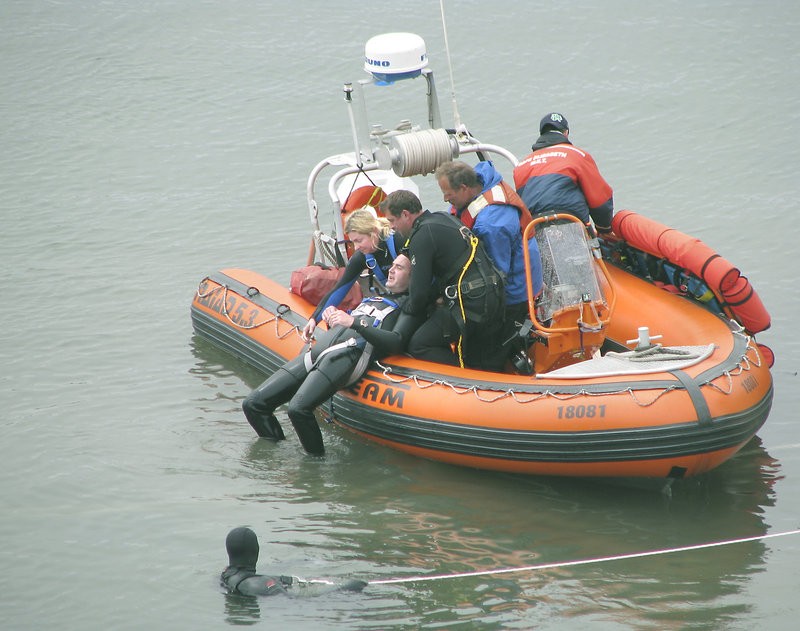 Rescue crews remove a 'victim' from the water during the full-scale aircraft emergency drill in the Fore River on Saturday.
