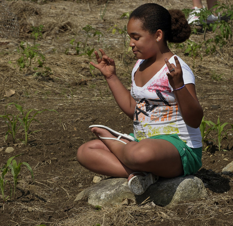 Mia White, 10, takes a yoga break after planting her share of sunflowers.