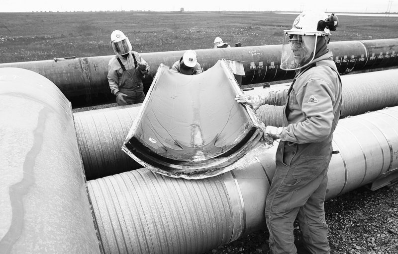 BP workers remove insulation from a pipeline at the Prudhoe Bay oil field on Alaska's North Slope in August 2006 so that the pipe can be ultrasound-tested for weakness due to corrosion. Five months earlier, 200,000 gallons of oil spilled from a hole in the pipeline.