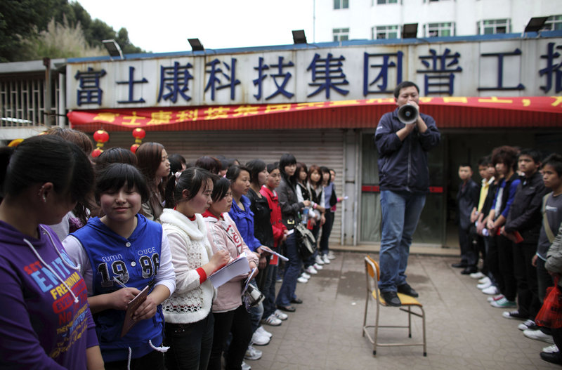 """A recruiter talks to job seekers near a sign which reads """"Foxconn Technology Group Recruitment Point"""" in Shenzhen, China. The firm has increased pay by up to 65 percent at its factories in Shenzhen."""