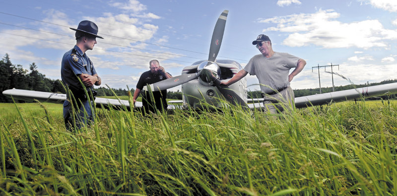 Pastor Todd Bell, right, speaks with Maine State Trooper Eric Verhille, left, as State Police pilot Wayne Ireland speaks with the Federal Aviation Administration Tuesday after Bell had to set his plane down in a hay field in Farmingdale.