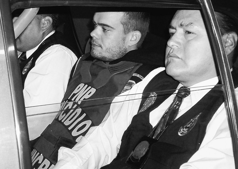 Joran van der Sloot, center, is seen in a police car in Lima, Peru, on Thursday. Van der Sloot confessed to killing a woman in his Lima hotel room on May 30, police said.