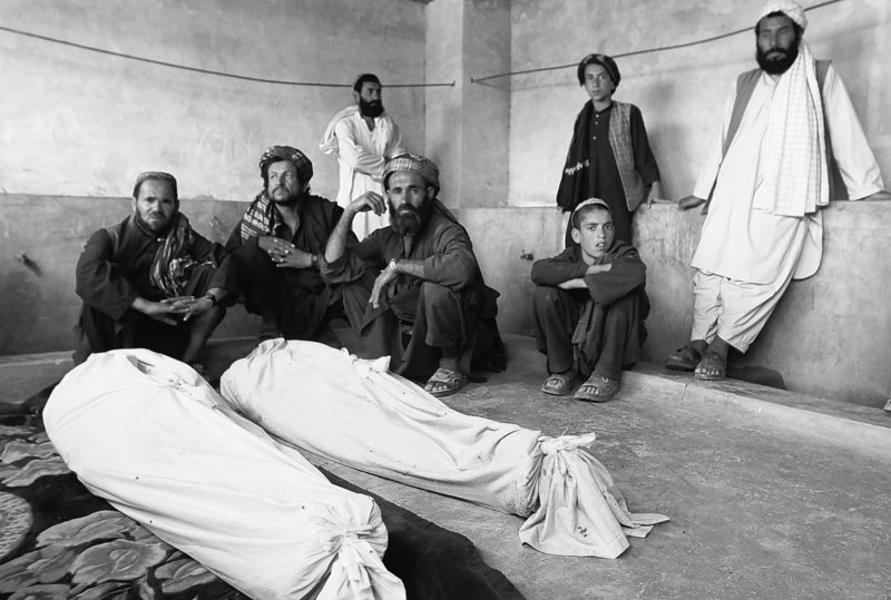 Afghan men gather on Thursday, near the bodies of people killed in Wednesday's blast in Kandahar's Argandab district. At least 40 were killed when an explosion ripped through a wedding party, an attack that NATO and the Afghan government say was a suicide bombing by the Taliban. Some local people, however, claim the extensive damage points to an airstrike by coalition forces.
