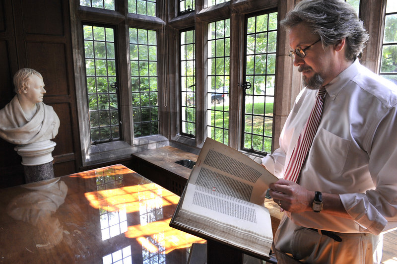 The Rev. John Runkle, conservator of Washington National Cathedral, leafs through a rare Dutch Bible. Runkle is being let go at the end of June, a casualty of the cathedral's third round of staff cuts to help balance the budget.