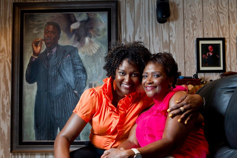 Rhonda McCullough, 51, right, wife of the late comedian Bernie Mac, and their daughter, Je'Niece McCullough, 32, pose near a portrait of Bernie Mac at home in Frankfort, Ill. Rhonda McCullough says that carrying on her late husband's quest to help those with sarcoidosis, the immune disease he suffered from, is her testament to the man he was.