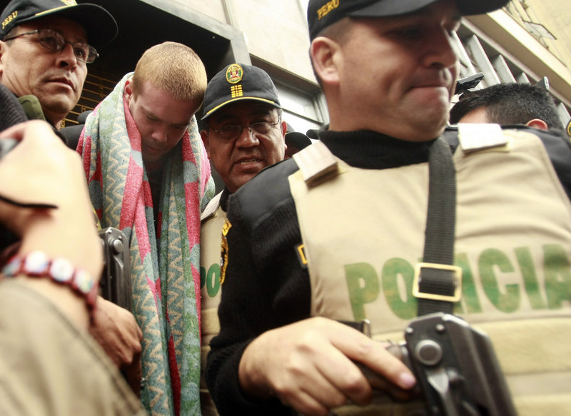 Joran van der Sloot, second from left, is escorted by police officers in Lima, Peru, on Friday. Peru's criminal police chief said that van der Sloot told interrogators he knows the location of the body of a U.S. teen who vanished on Aruba in 2005.