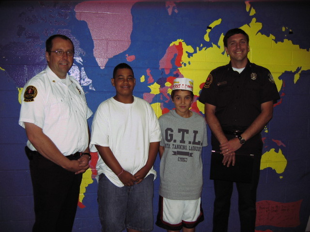 Isaiah Hall, center left, a fifth-grader at Lyseth Middle School in Portland, stands with Brent Rickett on Friday to receive the Everyday Hero award from the Portland Fire Department. On May 25, Isaiah saw Brent choking on a piece of egg during lunch and saved his friend by doing the Heimlich maneuver, which he had learned in health class. The boys are flanked by Fire Chief Fred LaMontagne on the left and Lt. Dan Small on the right.