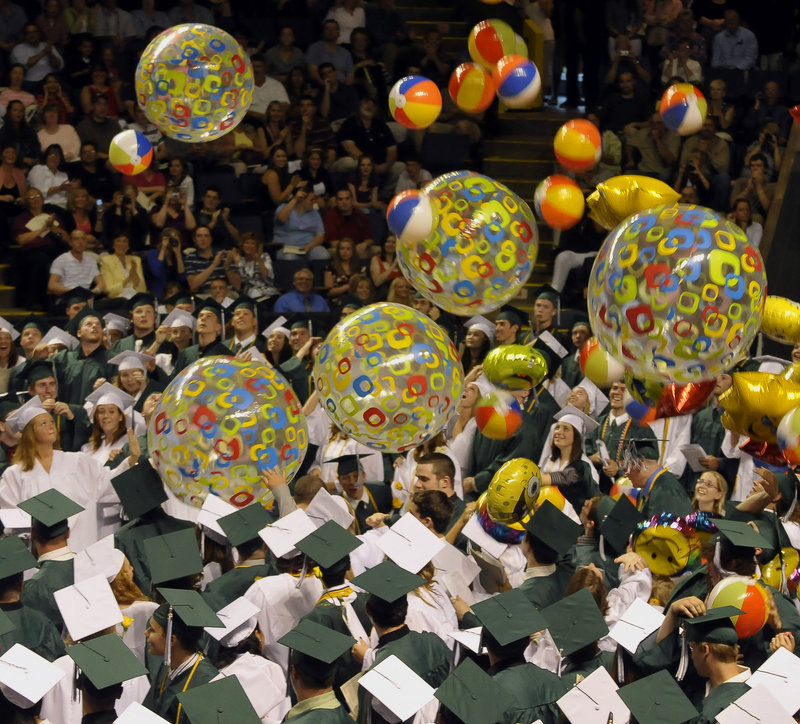 Family and friends applaud at the end of the ceremony as beach balls and balloons fall upon the graduates.