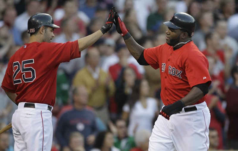 David Ortiz, right, is welcomed by Mike Lowell after scoring on Adrian Beltre's first-inning double Friday night for the Boston Red Sox in a 12-2 victory against the Philadelphia Phillies at Fenway Park.