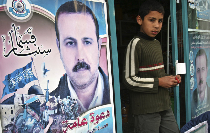 A Palestinian boy walks out of a store covered with posters of assassinated Mahmoud al-Mabhouh, a founder of Hamas' military wing, in Beit Lahiya, northern Gaza Strip. A man wanted in connection with the slaying has been arrested.