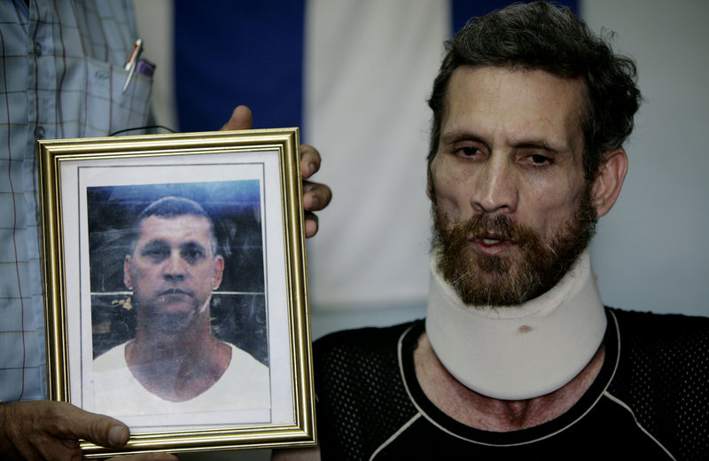 Ariel Sigler speaks with journalists after his release as a political prisoner in Cuba on Saturday. The photograph held next to Sigler depicts him before his arrest.