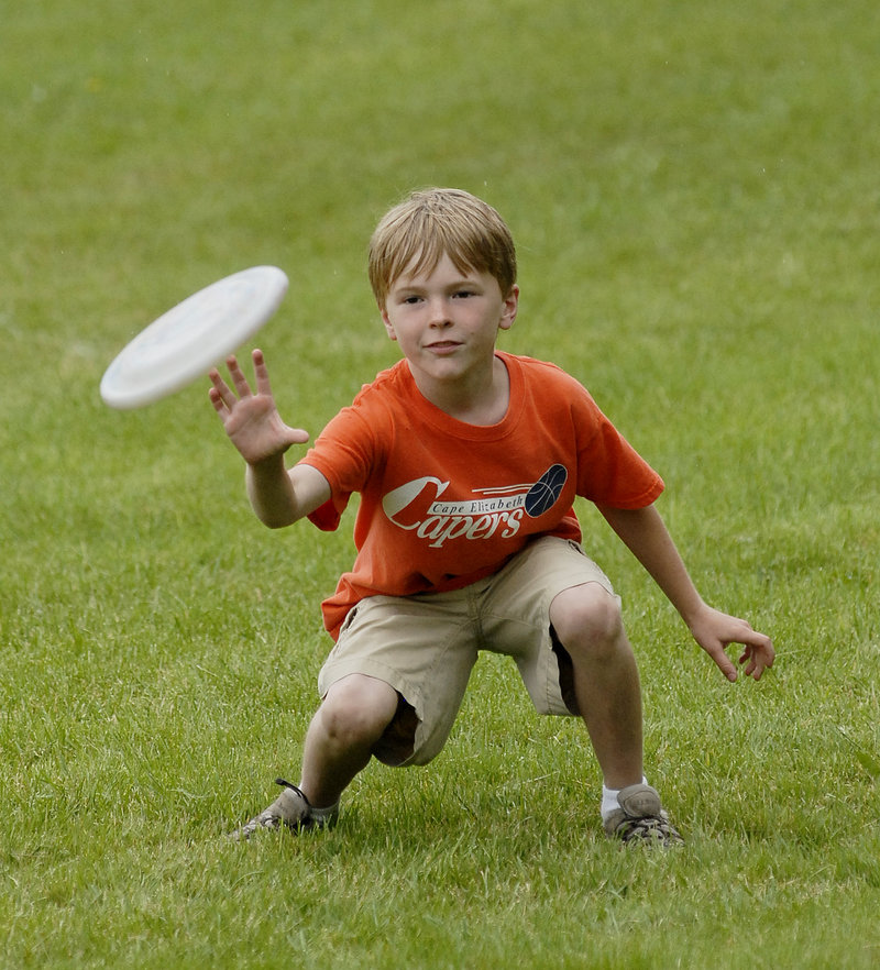 Alex Hansen, 8, reaches for a Frisbee while playing in the park.