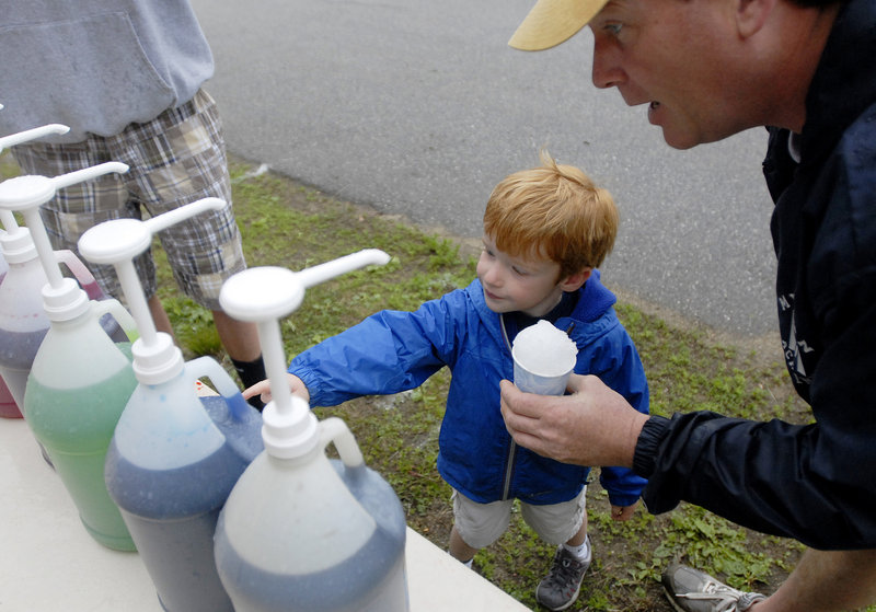 James Baldwin, 4, picks out a flavor for his snow cone with the help of his dad, Jon Baldwin.
