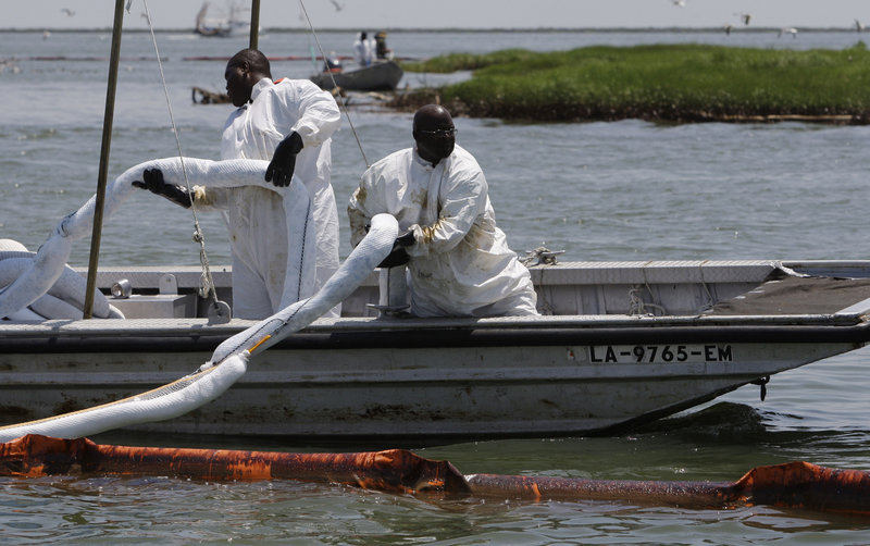 A crew replaces absorbent boom near a bird colony Saturday in Barataria Bay, La., to protect it from oil from the Deepwater Horizon spill. Unlike other countries, the U.S. doesn't require oil companies to have relief well plans before drilling for oil.